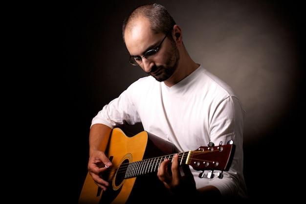 Hombre tocando la guitarra acústica