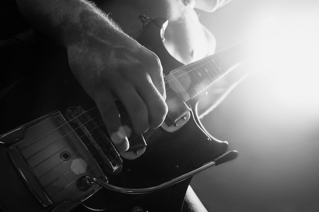 Hombre tocando la guitarra eléctrica en blanco y negro