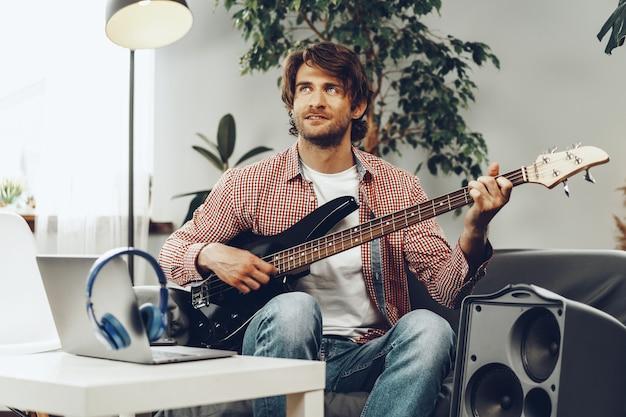 Hombre tocando la guitarra eléctrica y grabando música en un portátil