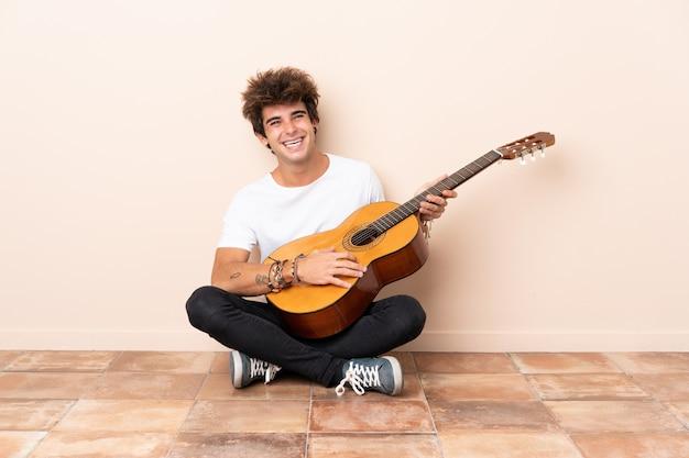 Hombre tocando la guitarra y sentado en el suelo
