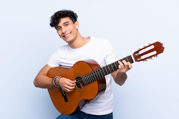 Hombre tocando la guitarra sobre pared aislada