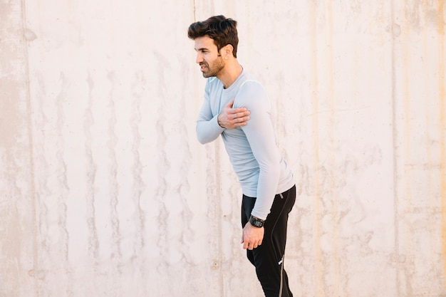 Hombre tocando el hombro lesionado