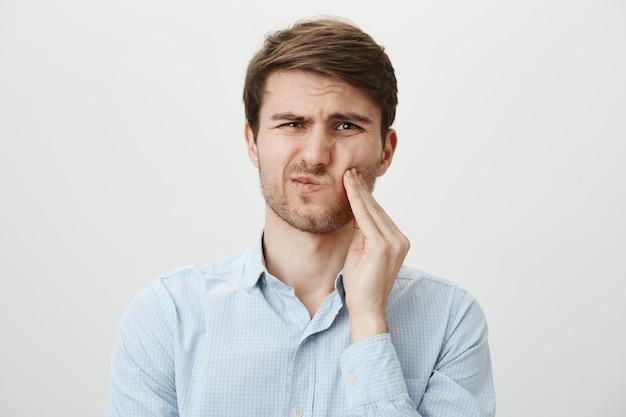 Hombre tocando la mejilla y haciendo muecas de dolor de muelas, necesita dentista