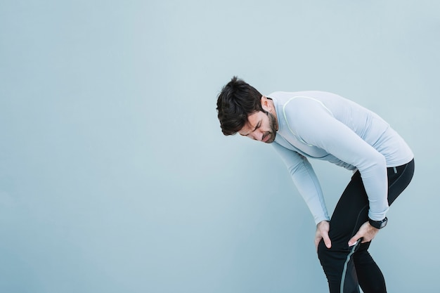 Hombre tocando la rodilla herida