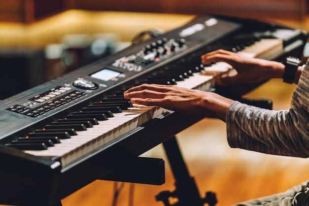Hombre tocando sintetizador electronico de teclado musical.