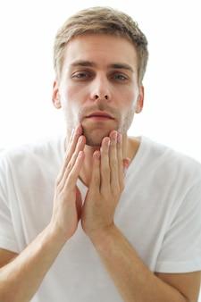 Hombre tocando su barba, listo para afeitarse.