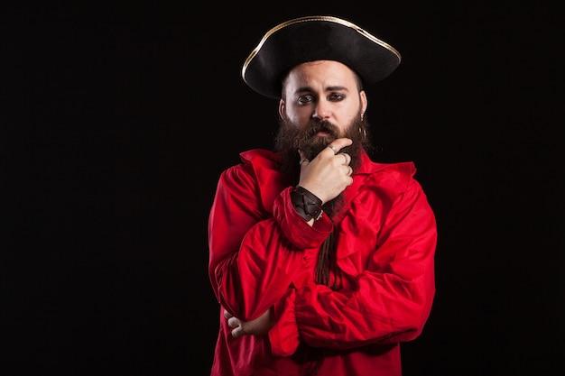 Hombre tocando su barba y luciendo como un pirata bárbaro para halloween. hombre mirando a la cámara.