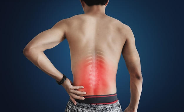 Un hombre tocando su espalda en el punto de dolor