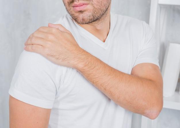 Un hombre tocando su hombro herido con la mano.