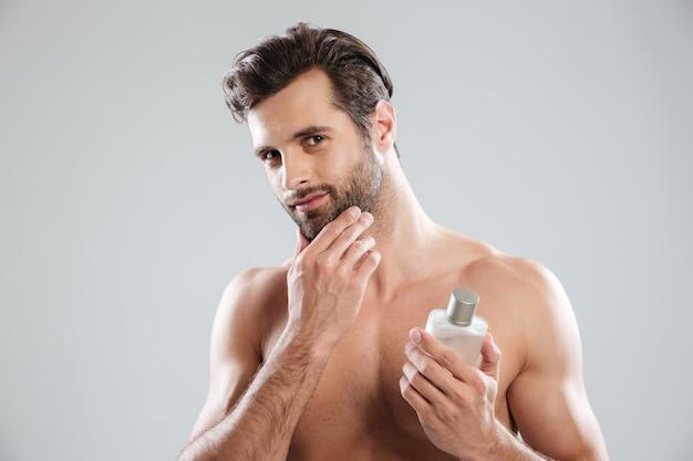 Hombre tocando su rostro mientras sostiene una botella de perfume