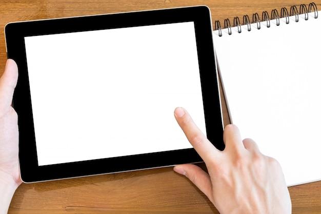 El hombre está tocando la tableta con pantalla maqueta blanca.