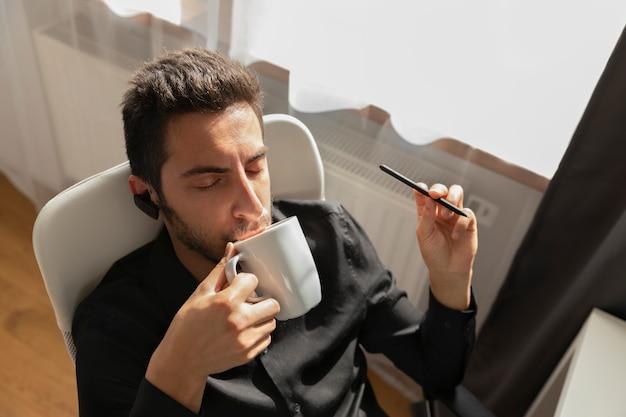 Un hombre toma café mientras trabaja en una computadora.