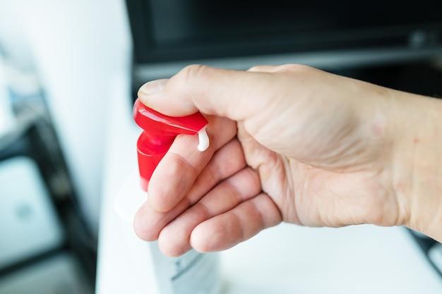 Un hombre toma una crema para la irritación y sequedad de la piel. máxima hidratación y suavidad de la piel de las manos.