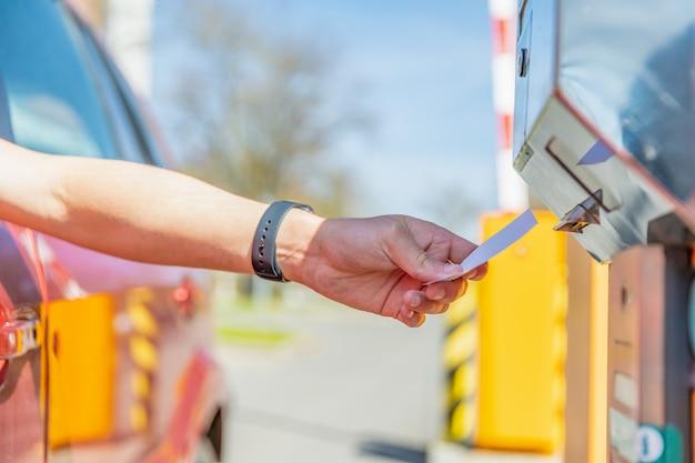 El hombre toma una multa de estacionamiento al ingresar al estacionamiento pagado en automóvil