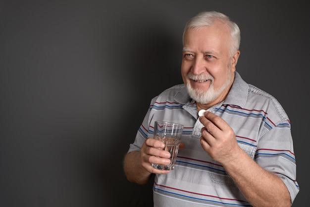Un hombre toma una pastilla de aspirina.
