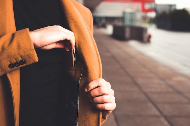 Hombre tomando una billetera del bolsillo interior de su abrigo