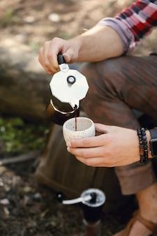 Hombre tomando café en el bosque