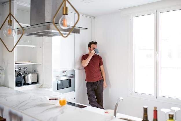 Hombre tomando café junto a las ventanas