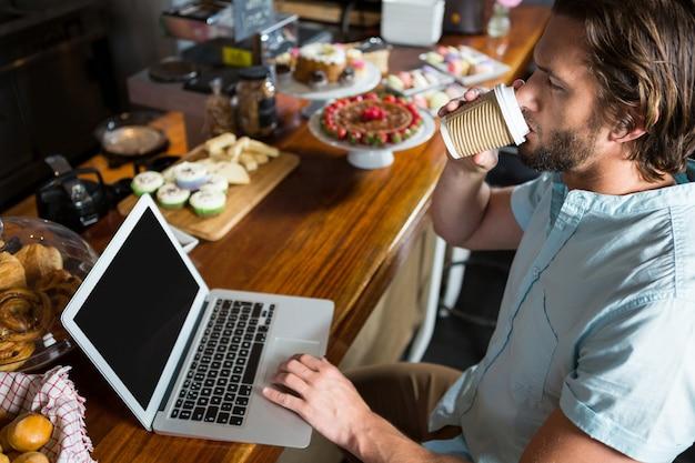 Hombre tomando café mientras usa la computadora portátil en el mostrador