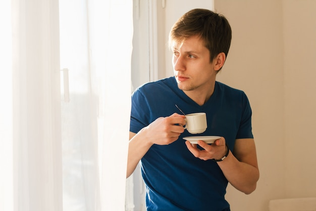 Hombre tomando café mirando por la ventana