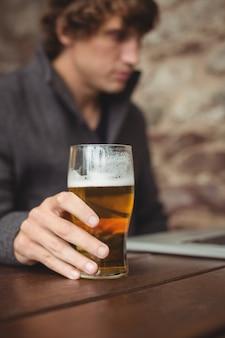Hombre tomando cerveza mientras usa la computadora portátil