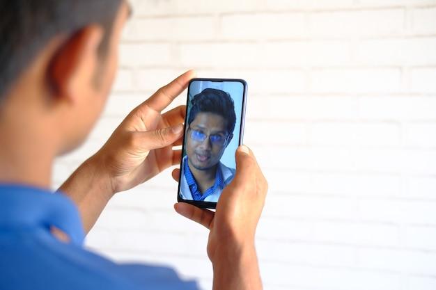 El hombre tomando consulta en línea con el médico en el teléfono inteligente.
