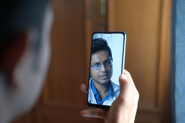 Hombre tomando consulta en línea con el médico en teléfonos inteligentes.