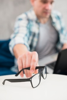 Hombre tomando elegantes gafas de mesa