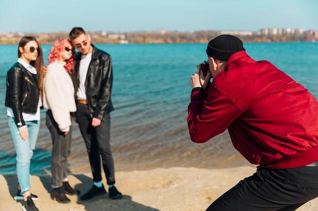Hombre tomando foto de gente joven.