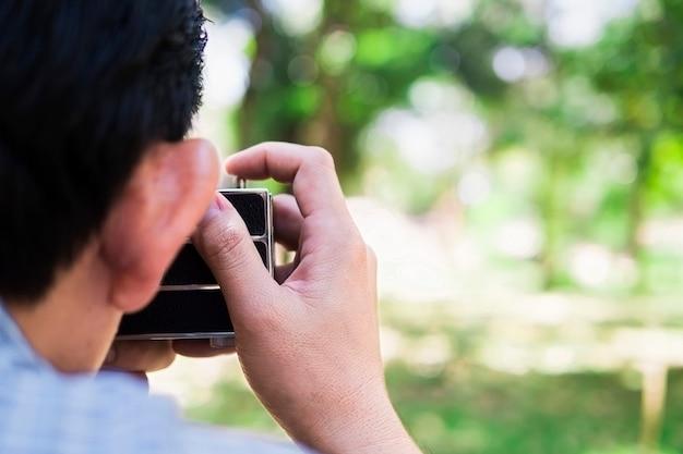 Hombre tomando foto usando vieja cámara retro