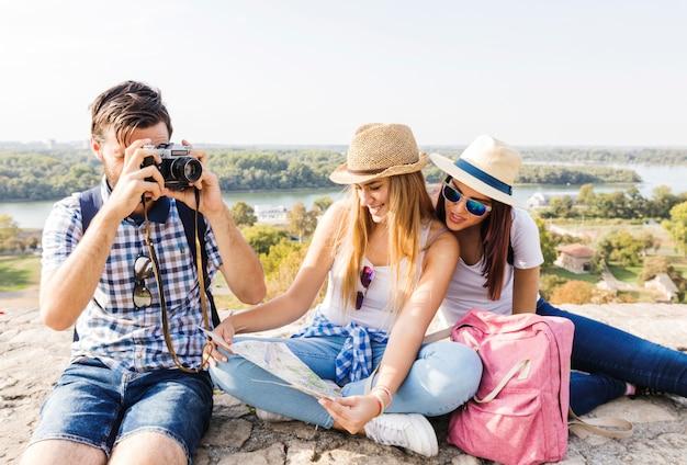 Hombre tomando fotos en la cámara cerca de sus amigas mirando el mapa