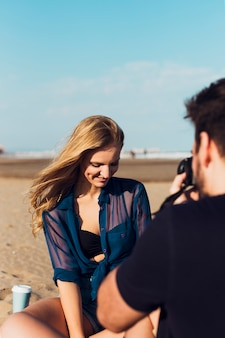 Hombre tomando fotos de mujer en la playa