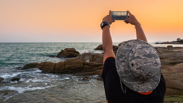 Hombre tomando fotos de la puesta de sol con teléfono móvil.