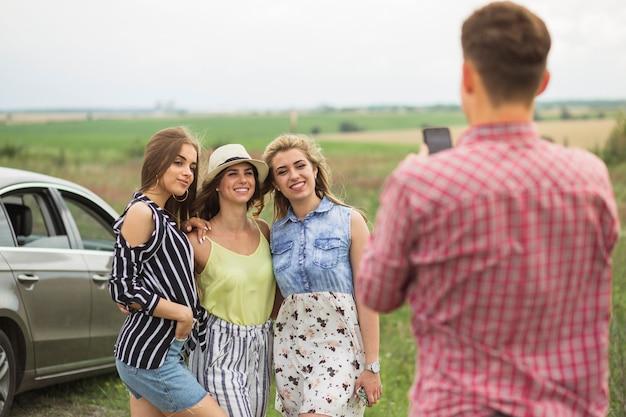 Hombre tomando fotos de tres amigas en el teléfono móvil