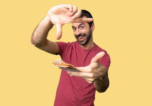 Hombre tomando mucho dinero enfocando cara. símbolo de encuadre sobre fondo amarillo aislado