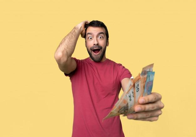 Hombre tomando mucho dinero con sorpresa y expresión facial en shock.