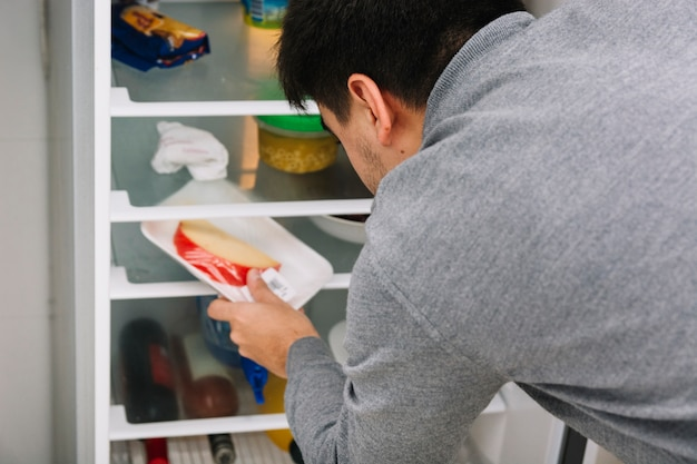 Hombre tomando queso del refrigerador