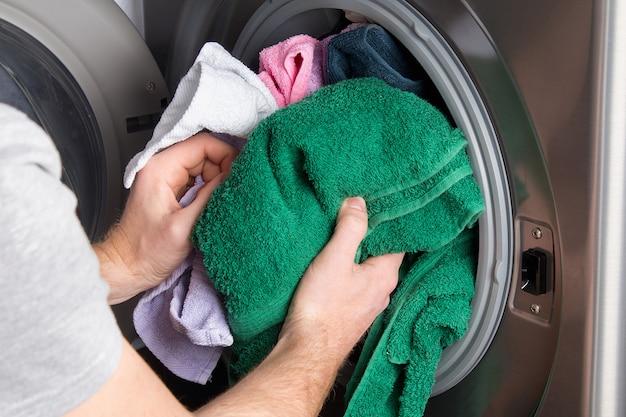 Hombre tomando ropa de color de la lavadora. tambor de lavadora lleno de ropa sucia en el baño.