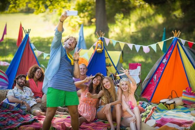 Hombre tomando una selfie con amigos en el campamento
