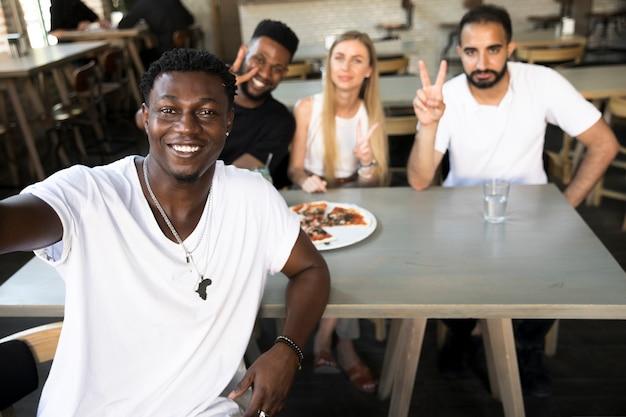 Hombre tomando un selfie con amigos interraciales