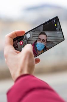 Hombre tomando selfie mientras usa máscara médica