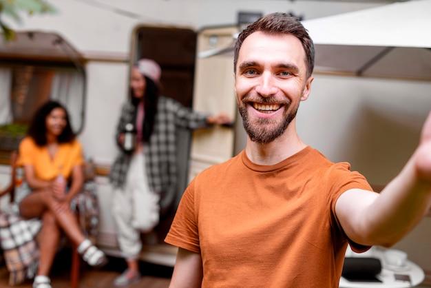 Hombre tomando un selfie y mujeres borrosas