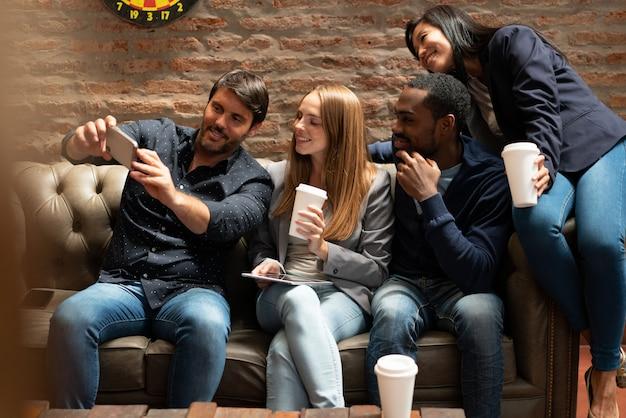 Hombre tomando selfie en sofá con co trabajadores