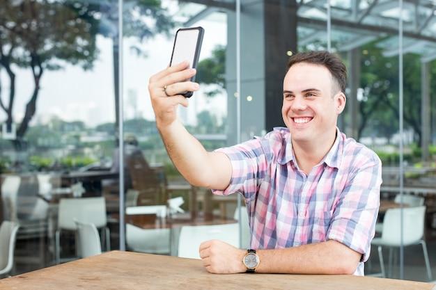 Hombre tomando selfie en teléfono inteligente en el café al aire libre