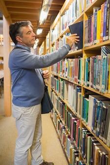 Hombre tomando un libro de los estantes