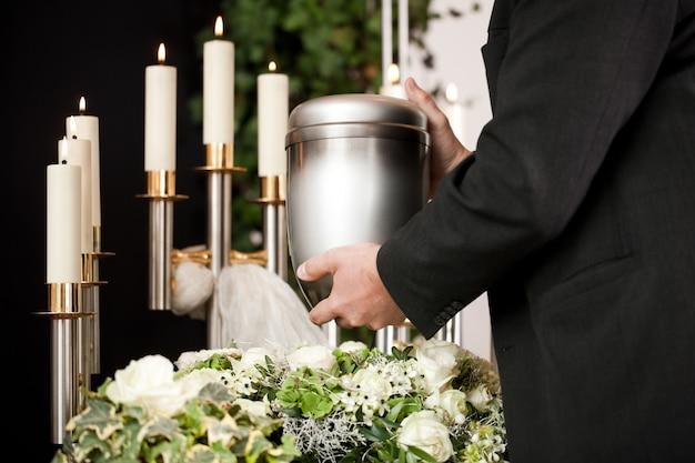 Hombre tomando urna funeraria con velas y flores.