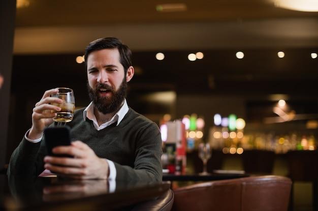 Hombre tomando un vaso de bebida mientras usa el teléfono móvil