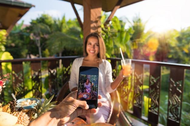 Hombre tomar foto de mujer con jugo en celular smart phone pareja