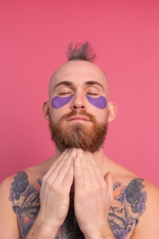 Hombre en topless tatuado barbudo guapo europeo con máscara de parches de ojos morados posando para la cámara en rosa