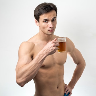 Hombre con topless de tiro medio tomando té